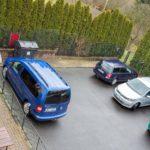 Pohled z okna penzionu na parkoviště s auty